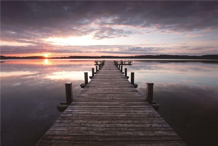 Foto Kunst Schilderijen: Uitzicht van een steiger over een meer bij avond zon